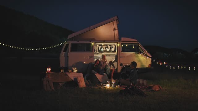 vídeos de stock e filmes b-roll de friends toasting wineglasses while camping at night - acampar