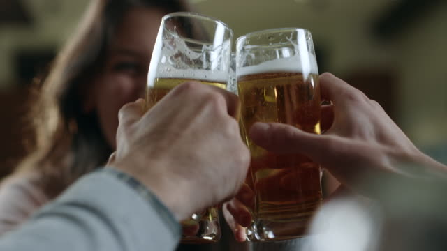 friends toasting with beer in cafe - celebratory toast stock videos & royalty-free footage