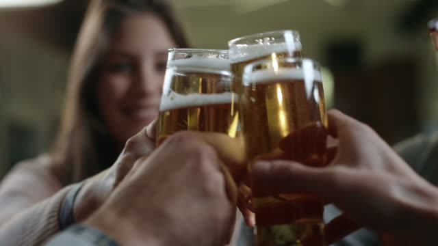 friends toasting with beer in cafe - bicchiere da vino video stock e b–roll