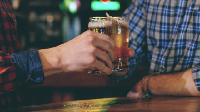 slo mo friends toasting with beer in the pub - table top shot video stock e b–roll