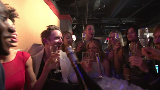 friends toasting with chamapagne in a nightclub lounge - spumante video stock e b–roll