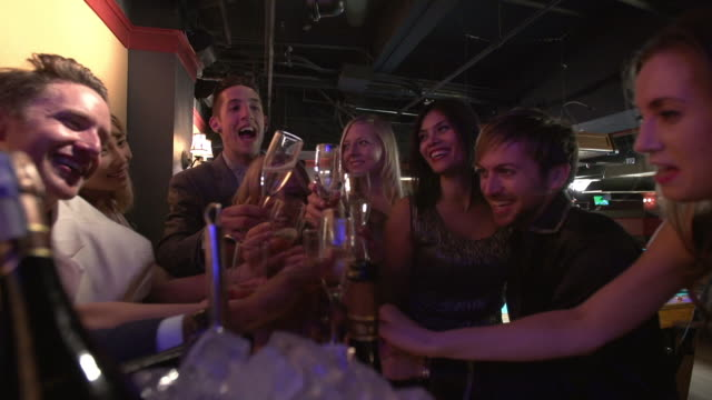 friends toasting with chamapagne in a nightclub lounge