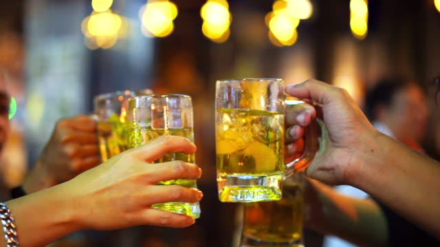 friends toasting with glasses of light beer at the pub. beautiful background of the oktoberfest. a group of young people while relaxing at the bar. fine grain. soft focus. shallow dof. - 乾杯点の映像素材/bロール