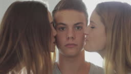 Friends together at home: teasing a guy with a kiss