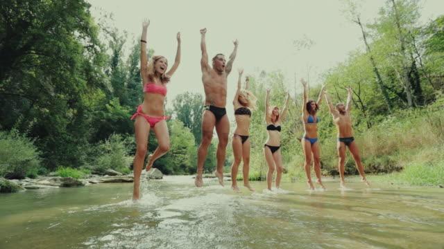 Freunde springen zusammen durch den Fluss