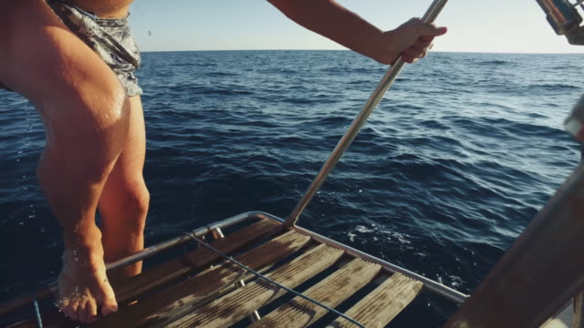 friends together on a yacht sailboat cruising the sea - sunbathing stock videos and b-roll footage