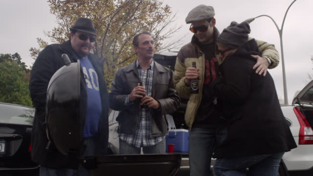 friends trying to stay warm at a tailgating party - beer cap stock videos & royalty-free footage