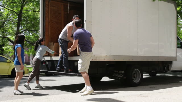 vidéos et rushes de ws pan friends unloading boxes from  moving truck on urban street / newark, new jersey, united states - véhicule utilitaire léger