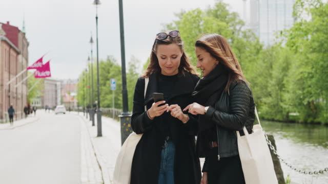 Amis utilisant une application de partage de trajet sur leur téléphone intelligent