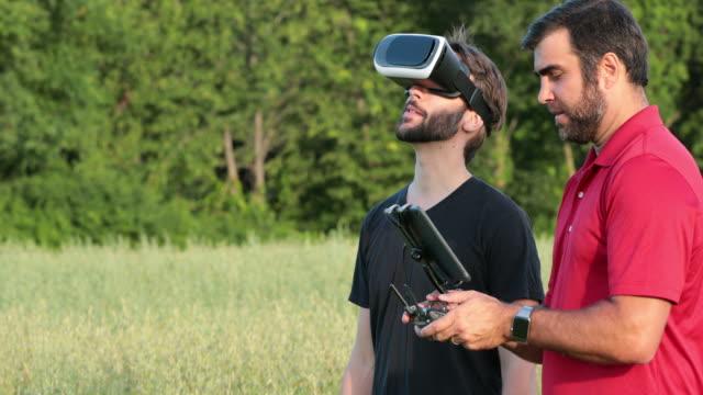 freunde mit drohnen und virtual-reality-kopfhörer bei sonnenuntergang - headset stock-videos und b-roll-filmmaterial