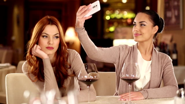 friends using their smart phones at the restaurant - dating stock videos & royalty-free footage