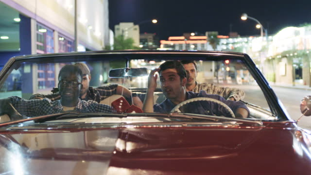 Friends waiting at stoplight in red convertible jam to radio, driver fixes hair in rearview mirror