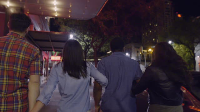 friends walk arm in arm through downtown austin, texas under flashing cinema marquee - cinema stock videos & royalty-free footage