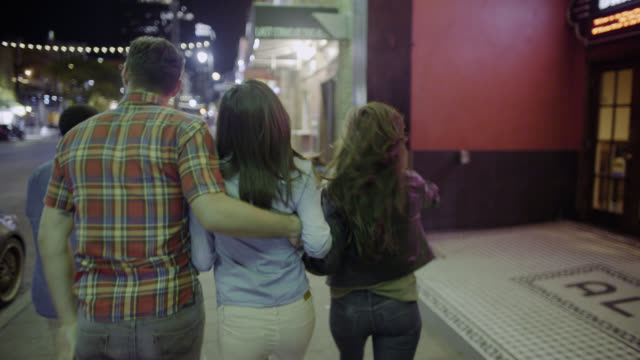 Friends walk arm in arm through downtown Austin, Texas under flashing cinema marquee