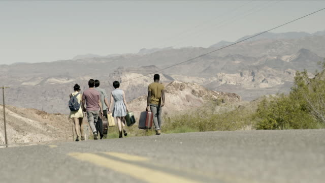 Friends walk away carrying luggage down scenic desert road