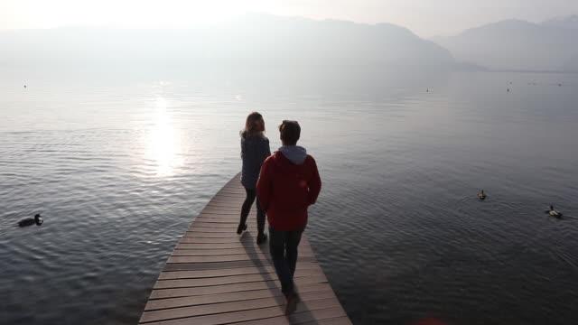 friends walk onto curving pier at sunrise - piemonte video stock e b–roll