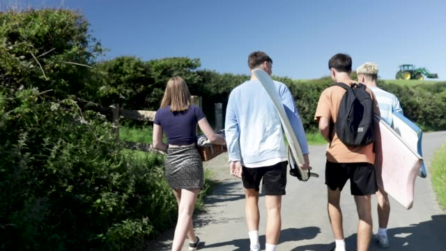friends walking down to the beach with surfboards. - eco tourism stock videos & royalty-free footage