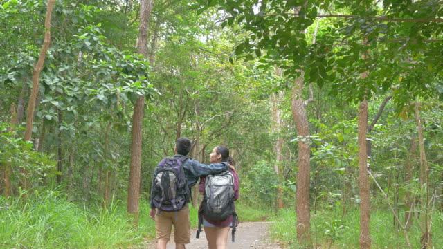Vrienden wandelen in het bos. Aziatische man en vrouw reizen buiten levensstijl in bos