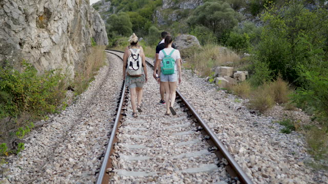 friends walking on railroad track in nature - tramway stock videos & royalty-free footage