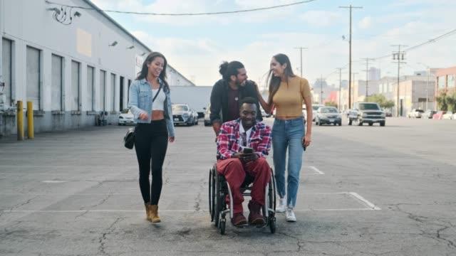 vidéos et rushes de amis marchant dans la rue de los angeles - chaise roulante