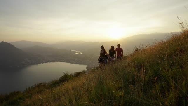 vidéos et rushes de amis, marche à travers les hautes herbes au coucher de soleil avec vue sur lac et ville ci-dessous - personne de race blanche