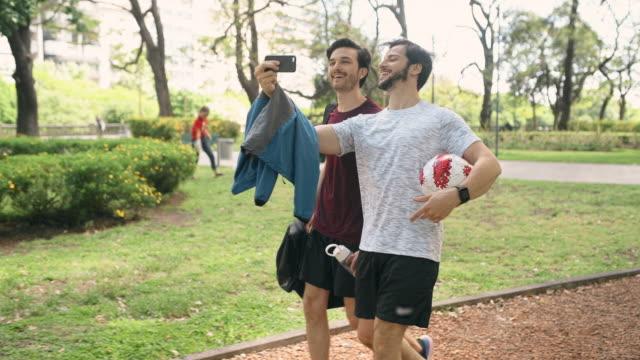 vidéos et rushes de amis marchant à la pratique de football - s'entraîner