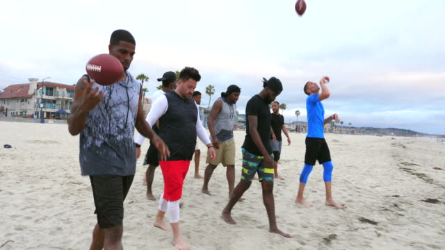 ms friends walking toward water after playing touch football on beach - touch football stock videos & royalty-free footage
