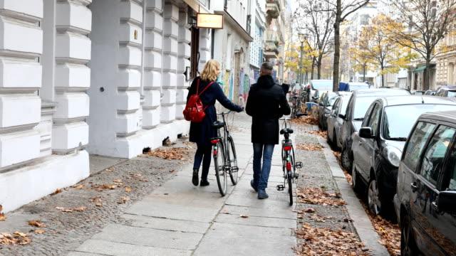 Freunde zu Fuß mit dem Fahrrad auf Bürgersteig in Stadt