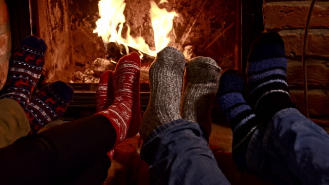 ds friends warming their feet by the fireplace - chalet stock videos & royalty-free footage