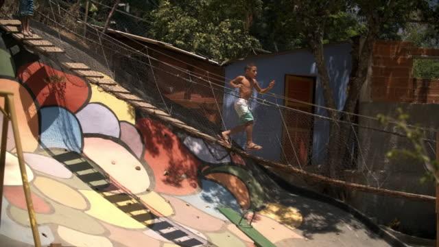 Friends watch as boy runs across swinging rope bridge