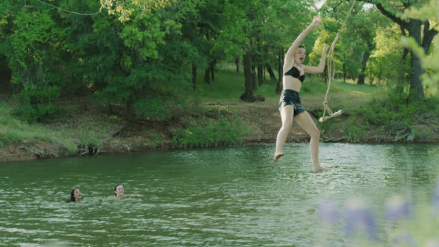 WS SLO MO. Friends watch as girl swings from rope swing and jumps into river.