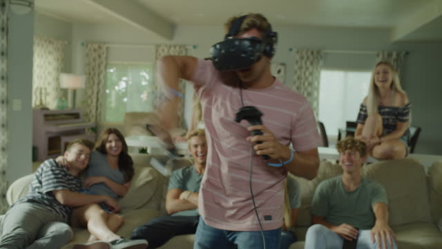 vídeos y material grabado en eventos de stock de friends watching boy wearing virtual reality goggles playing video game / cedar hills, utah, united states - realidad virtual