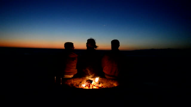 Friends Watching the Sunset at Beach Bonfire