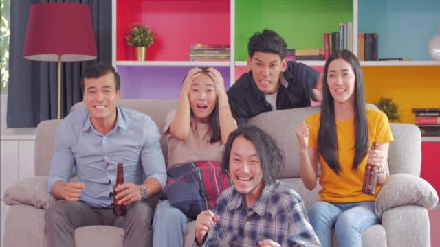 vídeos de stock, filmes e b-roll de amigos em casa a ver tv e beber uma cerveja gelada. tela sports.lifestyle: marcos & celebrações - termo esportivo