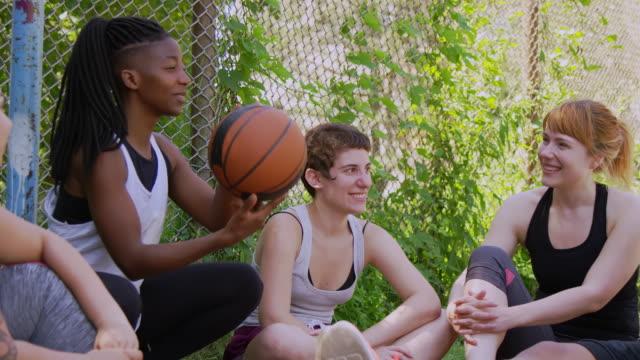 vidéos et rushes de amis observant la femme essayant de tourner le basket-ball - streetball