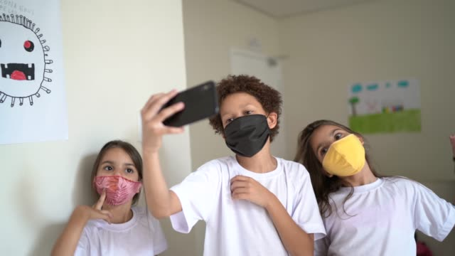 friends wearing face mask vlogging during breack time at school - prevention stock videos & royalty-free footage
