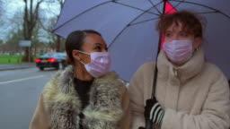 Friends Wearing Masks Walk Under Umbrella Together Slow Motion