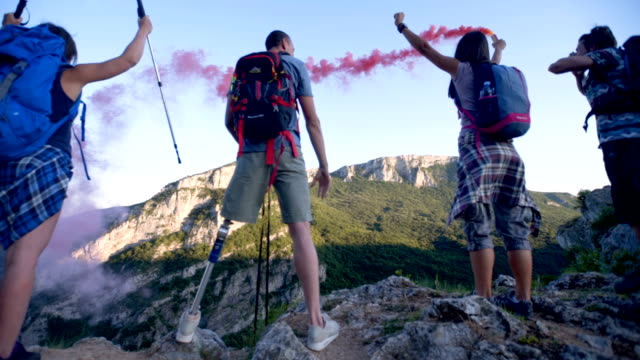 friends with a smoke bomb on top of the mountain - prosthetic equipment stock videos & royalty-free footage