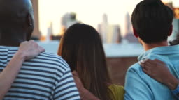 Friends with arms around looking from rooftop, back view