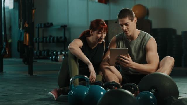 freunde mit digital-tablette in turnhalle - trainingsraum wohnraum stock-videos und b-roll-filmmaterial