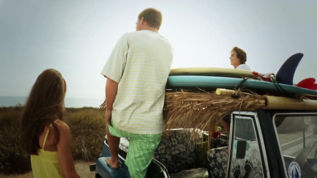 ms friends with giving high five each other and getting surfboard off roof rack / laguna beach, california, usa - 手をかざす点の映像素材/bロール