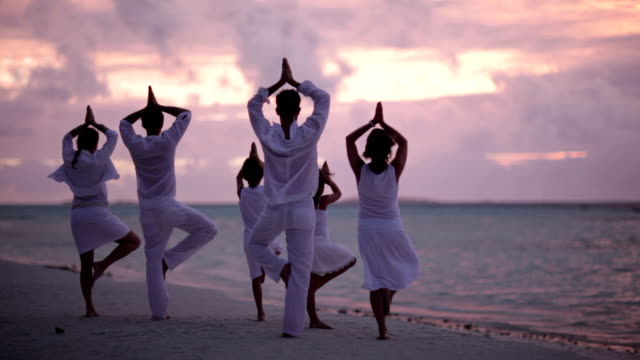 friends with kids doing yoga at sunset on beach