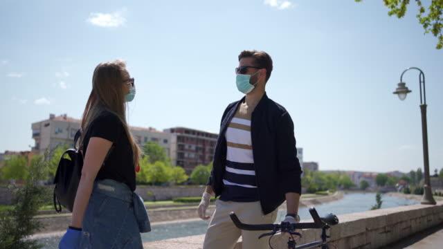 vidéos et rushes de amis avec des masques protecteurs et des gants saluant avec des coudes pendant la pandémie de coronavirus - accident et désastre