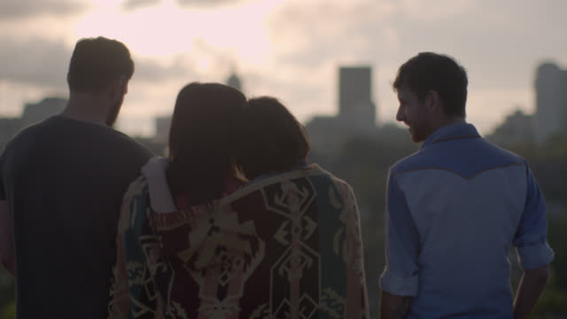 stockvideo's en b-roll-footage met friends wrapped in quilt put arms around each other and watch the sun set over downtown austin, texas - dak