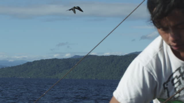 Frigate birds flying near fishing boat. Fisherman in foreground, Indonesia, 2012