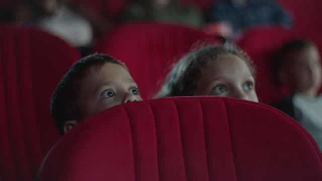 frightened boy and girl hiding behind seat in cinema - school child stock videos & royalty-free footage