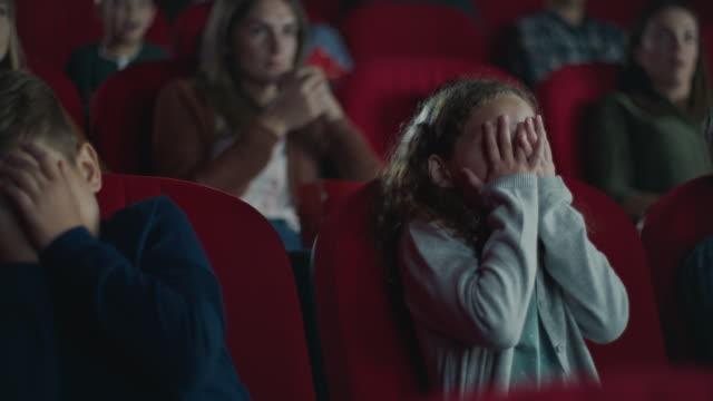 frightened boy and girl in cinema - industria cinematografica video stock e b–roll