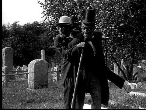 1916 b&w ms frightened man in top hat putting older man with injured foot down from piggyback position in graveyard/ men holding still as if hearing sound  - piggyback stock videos & royalty-free footage