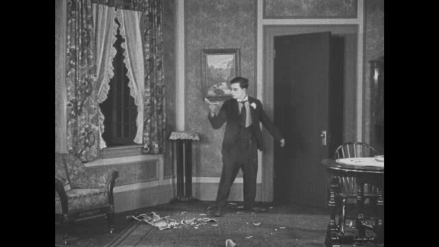 1921 frightened man (buster keaton) watches as door closes itself and vase is shot out of his hand - anno 1921 video stock e b–roll