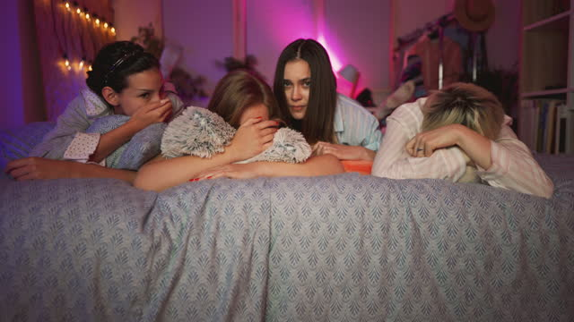 frightened young girlfriends at sleepover watching a horror movie on a tv - slumber party stock videos & royalty-free footage